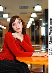 Young girl sorrowful dressed in red blouse sitting in empty...