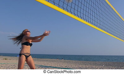Young girl spends summer vacation on the beach playing volleyball