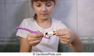little eight-year-old girl in white t-shirt squeezes toothpaste on brush and prepares to brush teeth. Health care, hygiene, childhood concept. Caries prevention. Morning or evening routine in bathroom