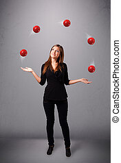 young girl standing and juggling with red balls - pretty...