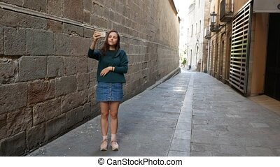 Young girl standing at european street and taking a shot of...