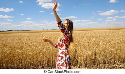 young girl standing in a field looking up at the sky and lets blow bubbles