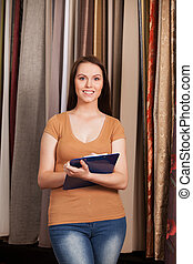 young girl standing in dry goods store. beautiful brunette working in fabric store