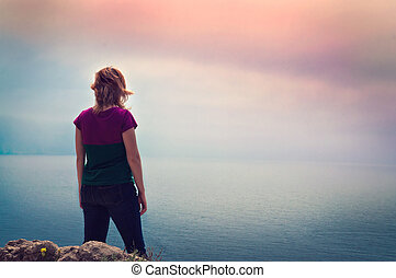 young girl standing on a cliff above the sea