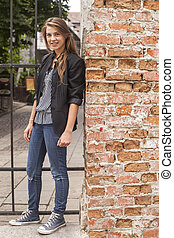 Young girl standing on a street near the brick wall.