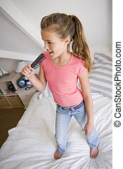 Young Girl Standing On Her Bed, Singing Into Her Hairbrush
