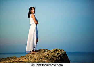 Young girl standing on rock near sea.