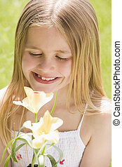 Young girl standing outdoors holding blossom smiling