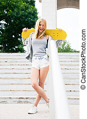 Young girl standing with skateboard
