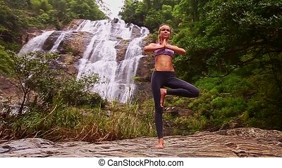 Young Girl Stands in Yoga Pose against Waterfall Plants
