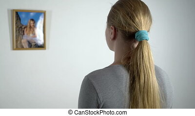Young girl staring at photo of a little girl in frame hanging on the wall