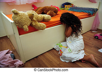 A young girl who is a victim of domestic violence cries on the floor of her bedroom