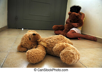 A young girl who is a victim of domestic violence sits on the floor next to the front door and gets comfort from her teddy bears