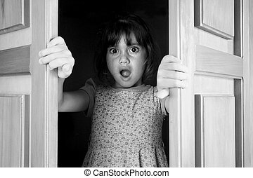 Young girl (age 6-7)surprised to find and see what is behind closed doors. Children childhood concept. Real people copy space (BW)
