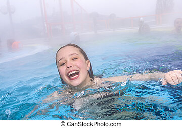 young girl swims in the outside area of a thermal pool in...