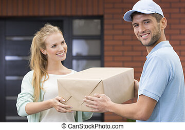 Young girl taking a delivery form handsome courier in blue uniform