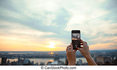 Young girl taking a photo from the roof