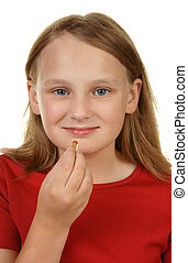 young girl taking a pill