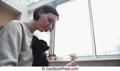Young girl taking selfie with cute black pet chihuahua lap...