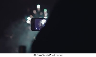 Young girl taking video to fireworks on smartphone. Close up...