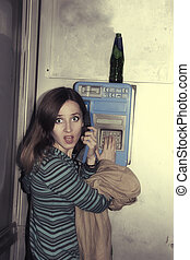young girl talking in public pay telephone - The young girl...