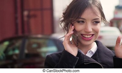 Young girl talking on mobile cell phone smiling, outdoors. Happy Woman Talking On Smart Phone in the street