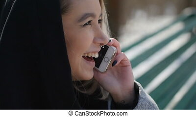 young girl talking on the phone while sitting on a bench in the park