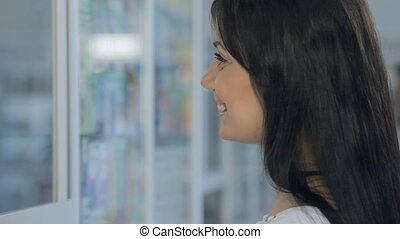 Young girl talking to a pharmacist in a drugstore - Young...
