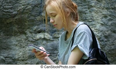 Young girl talking to someone on the background of a stone wall