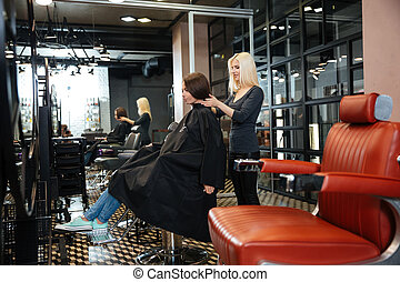 Young girl talking with hairdresser in beauty salon