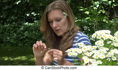 young girl tearing daisy petals in green park. 4K - close up...