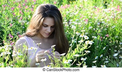 girl tells fortunes on a camomile flower on the meadow