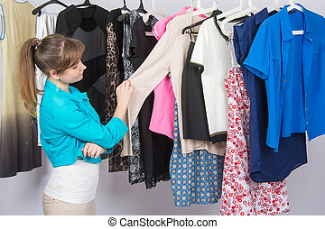 Young girl thoughtfully chooses clothes in a wardrobe