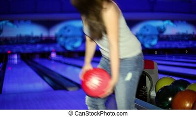 Young girl throws bowling ball to beat skittles in dark club