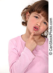 Young girl touching her chin with her finger
