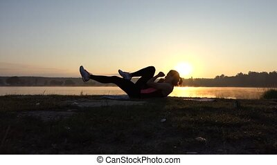 Young Girl trains her abs at sunset near lake.