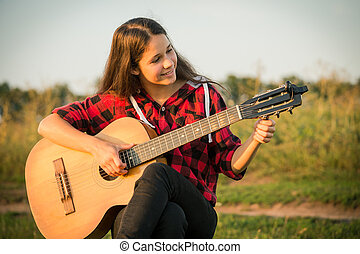 Young girl tunes the guitar on meadow at sunset