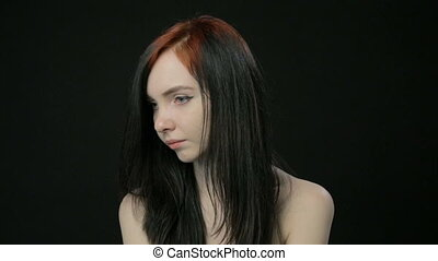 Young girl turned head on black background