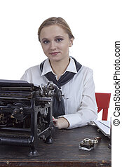 Young girl typist with an old typewriter on a white background