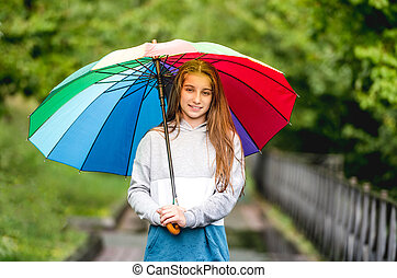 Young girl under colorful umbrella