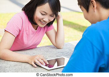 young girl using a tablet  with a friend or sweetheart