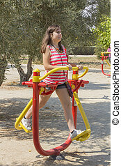 Young Girl using an exercise machine in a park