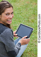 Young girl using her tablet computer while sitting on the grass and beaming