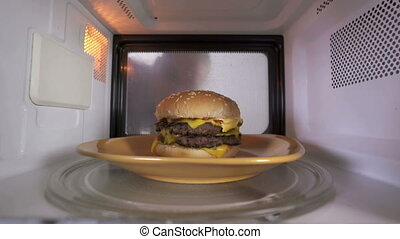 Young girl using microwave for reheating cooked double cheeseburger