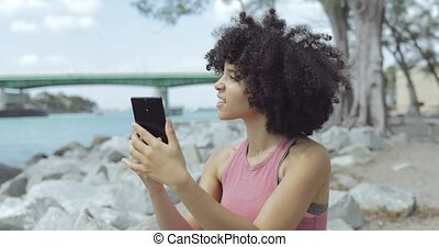 Young girl using phone for selfie on riverside - Black curly...