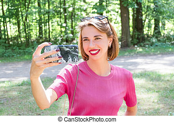 Young girl using smarthone - Young cute cheerful girl in...