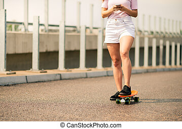Young Girl Using Smartphone on the Skateboard