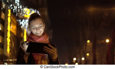 Young girl using tablet at night on the bright street with lights. 4K