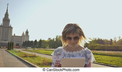 Young girl using tablet outdoor and smiling. Girl using digital tablet pc in the park. Student using tablet after school.