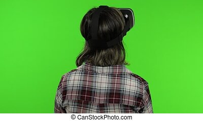Young woman using VR app headset helmet to play simulation game. Watching virtual reality 3d 360 video. Isolated on chroma key green background in studio. Girl in VR goggles looking around